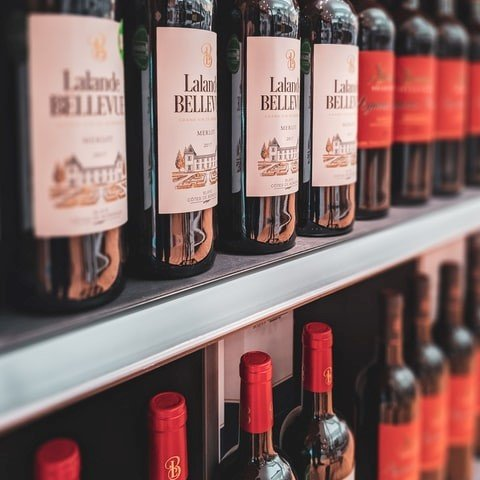 Butelki czerwonego wina wyeksponowane na półkach. Zdjęcie pochodzi z https://unsplash.com/photos/Z5AKtkHRjsQ